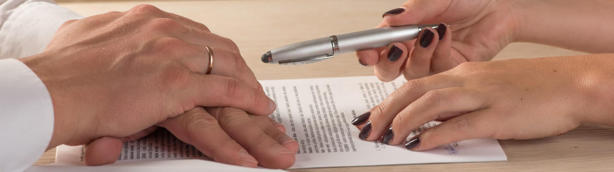 Husband and wife signing divorce papers - Stoddard Law Office